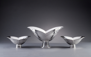 Silver centerpiece and garniture of V-shaped, leaf-like volumes with striped incisions atop bases formed of concentric circular rings.