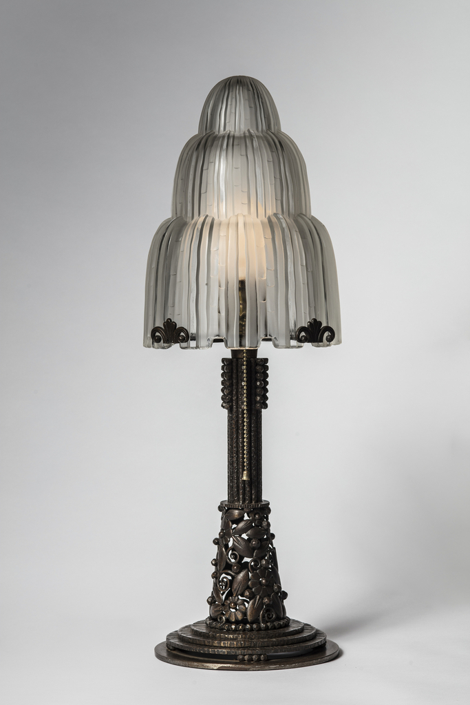 Lamp with stepped, wrought-iron base upon which a fluted column springs from stylized foliage and curling vines to support a cascading glass shade accented by wrought-iron art deco palmettes. The round bulb is controlled by a beaded brass cord that glints against the dark, dappled texture of base.