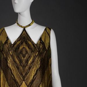 Collared dress with geometric detailing of intersecting and overlapping diamonds.