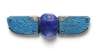 Belt buckle in the shape of a scarab with outstretched wings; the insect's blue Egyptian faience body is accented by incised linework and accented by diamonds and cabochon sapphires and wrapped by a layer of black enamel. Base of gold and platinum.