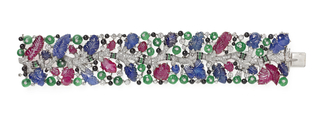 Platinum bracelet featuring a winding central diamond pavé branch from which leaves and fruits of incised sapphire and ruby grow, surrounded by galaxy of diamonds, cabochon emerald, and onyx circles.