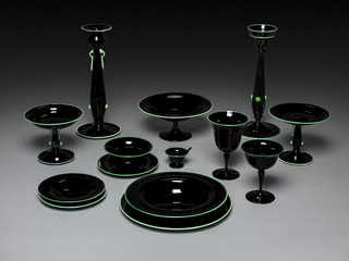 Black glass pair of mismatched candlesticks and single dinner service with acid green glass overlay; object perimeters are perfectly circular while volumes gently undulate, terminating in wide lips. The candlesticks and smaller stemmed dishes have additional green ornamental elements.