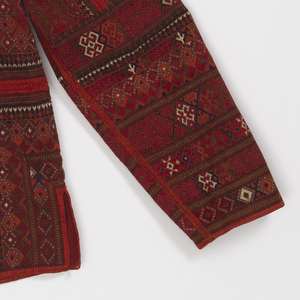 Short jacket of black wool solidly covered in geometric decoration, largely embroidered, in bright wool of red, orange, green, bright blue, and white. The jacket is comprised of perpendicular panels that are divided by bands of orange embroidery. The coat has been re-cut to fit the donor. Lined with red silk over original lining of cotton.