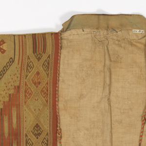 Hand-sewn coat made of two lengths of cloth horizontally stitched together around the middle with unshaped rectangular pieces attached to the slits for sleeves, which hang from the middle of the arm. A small collar band is attached to the back of the neck. Colors are dark red, gold and dark yellow in a pattern of stripes with chevrons running between. The upper part of the garment has a shaped design of geometrical and floral units. Coat is lined and narrow braid covers all outside seams.