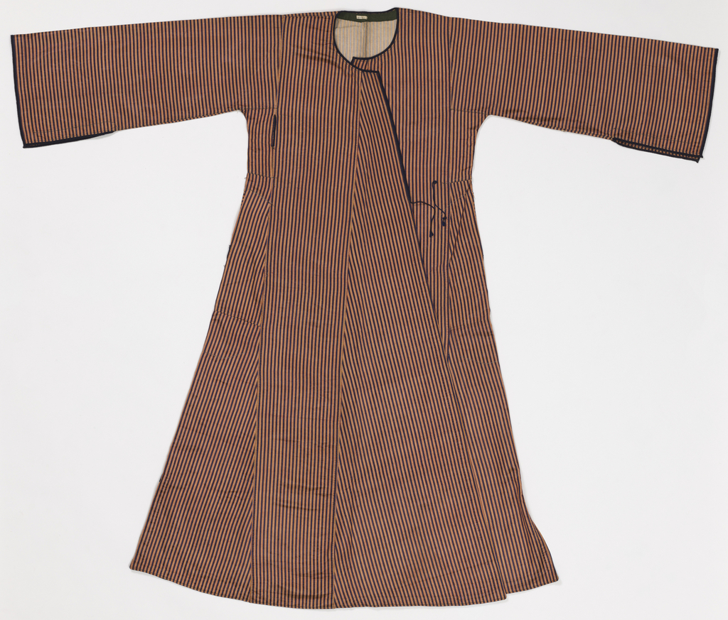 Long outer coat of silk with a cotton lining. Coat is in satin weave with stripes of dark blue, red and yellow. Blue braid edges collar and wide sleeves. Undershirt is white creped cotton and hand-sewn with a round collarless neck. White cotton drawers, very wide, have a drawstring tie.