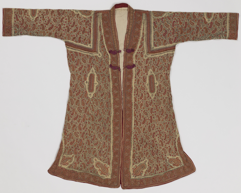 Robe open down center front with two purple frog style closures at chest. Robe has long sleeves and slightly flared skirt with short side slits. Robe is pieced together, with braid embellishment along seam. Overall paisley and vine motifs worked in red, greens, blues, and yellow on a white background. Lined in beige silk.
