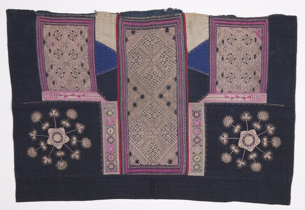 Baby carrier of deep indigo-dyed cotton, embroidered with three rectangles of complex lozenge patterns in white, with borders of pink, white, and blue embroidery. In the lower left and right corners, starburst designs embroidered in white.