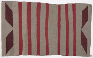 Gray blanket with wide red bands and two chevrons of narrow black and red stripes at each end.