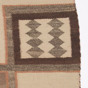 Off-white blanket with five rectangles of geometric pattern: Four corners are gray diamonds on an off-white ground surrounded by concentric squares of brown, gray and peach. Center is brown, peach and tan zigzags bands with border of gray and peach concentric squares.