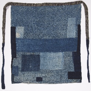 Apron composed of repurposed patches of indigo-dyed cotton fabrics.