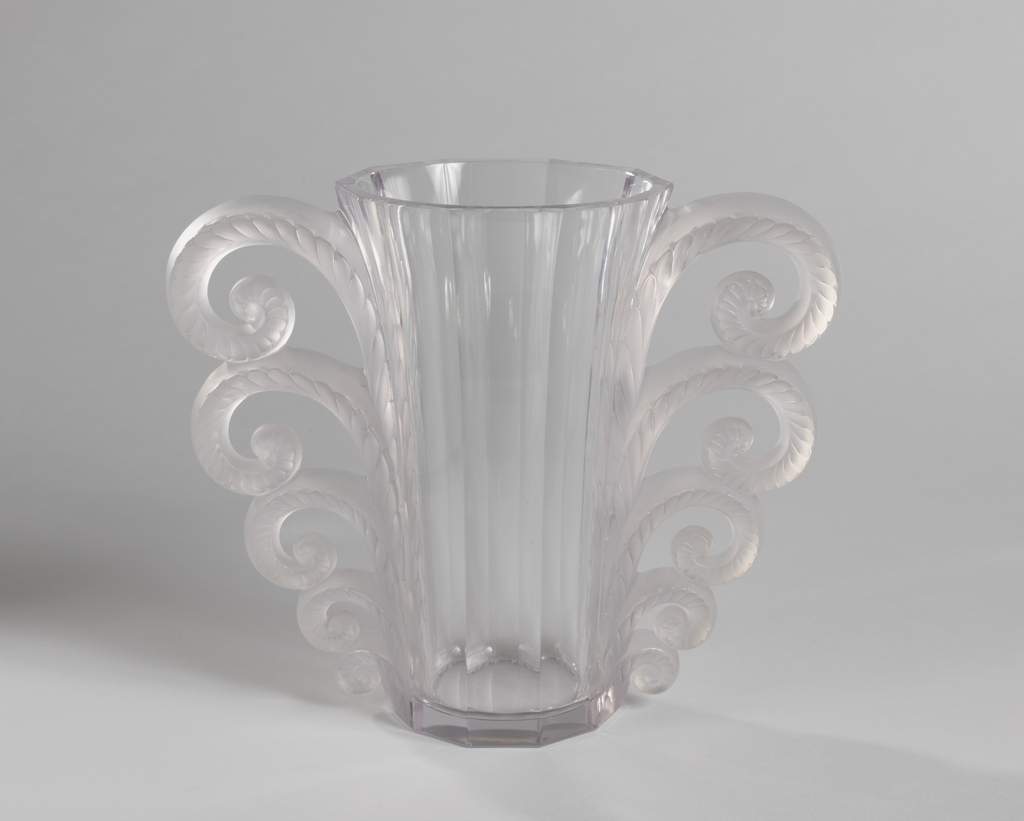Tall, slightly flared footless vase of clear glass with ten paneled sides.  On two opposite sides are handles in form of graduated satin-finished scrolls with slightly oblique grooving at edges.