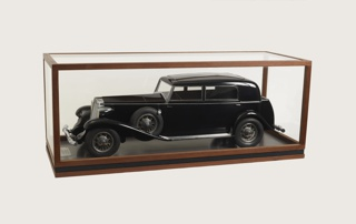 Black sedan with chromed grille, headlights, bumpers, running boards, window frames, and door handles; rubber tires with chromed hub caps; two spare tires mounted on either side, at front fenders. Model mounted on flat wooden base with metal plaque mounted at front. Removable plexiglass and wood cover fits on base.