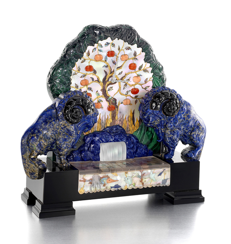 Clock depicting the Tree of Knowledge with precious stone fruits standing in for numerals against a mother-of-pearl ground. Clock face flanked by stylized lapis rams in between which a lapis fountain spills frosted glass into a pool of inset sea creatures, all on a rectilinear onyx plinth.