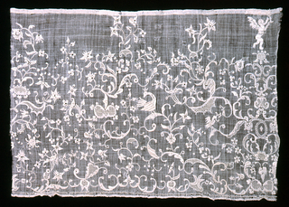 Wide border of linen with areas of drawn work and embroidery in an open pattern of floral sprays and birds with an angel on the right side.