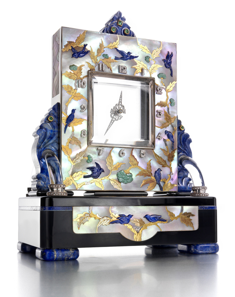 Rectangular mother-of-pearl frame inlaid with precious stones and gold surrounds a beveled rock crystal clock face with diamond-encrusted hands and numerals resting on an onyx base with additional inset decoration with lapis volute accents and feet.