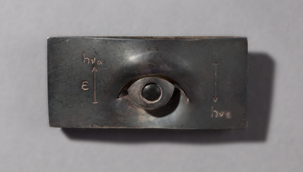 Roughly rectangular dark brooch with a scupltural eye in center flanked by numerals and an up-facing arrow on the left and a down-facing arrow on the right.