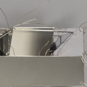 Rectangular open metal form with highly reflective surfaces; flexible wires projecting from points along edges.