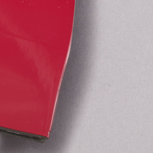 Contoured, rectangular piece of stainless steel cut from an E-class 210 Mercedes Benz in glossy bright red; reverse having two straight pin closures with circular caps.