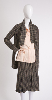 Suit in beige and brown wool knit; fluttering collar and fluted, columnar skirt.