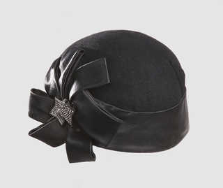 Black felt cloche hat with thick silk band and geometric bow garnished by abstract, angular leaves with rhinestones.