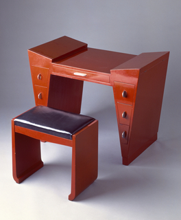 Red-lacquered wood dressing table and bench of geometric form; dressing table with hinged, covered storage wells at top of each tapering leg, and three drawers below, each with semi-circular metal pull; one wide drawer in center with horizontal metal tab pull; bench with rectangular black leatherette seat cushion.
