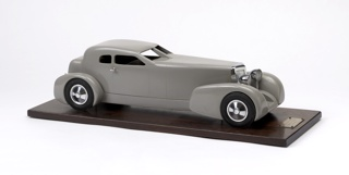 Gray coupe with long tapering hood and projecting box-like trunk; chromed grille, headlights, tail lights and door handles; four black-painted metal wheels with chromed hub caps. Model mounted on flat wooden base with metal plaque mounted at front.