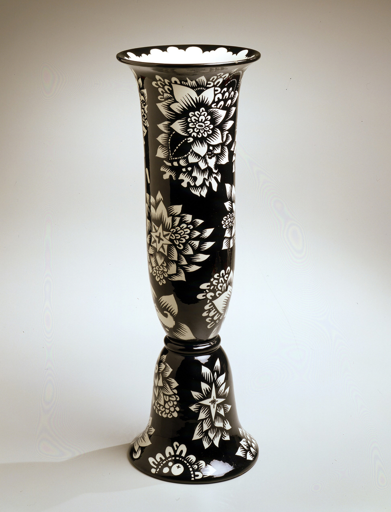 Tall molded white earthenware vase with wide lip and white floral and leaf decoration against a black glazed ground; shape of foot is an inverted echo of the main volume's silhouette.