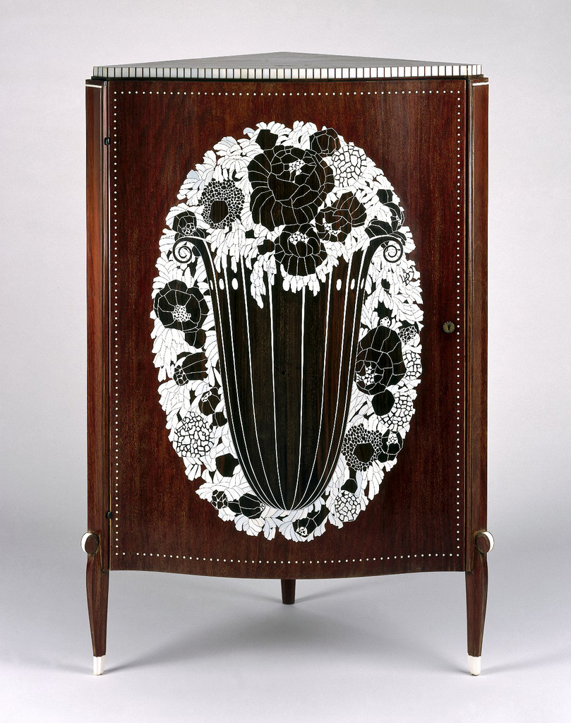 Corner cabinet with mahogany carcass veneered in amaranth with ivory inlay decoration; at center, a large urn with scrolling volutes holds a burst of marquetry blossoms and greenery which extend beyond the volume and surround the vessel. Inlaid ivory dots and rectangles wrap the piece's various borders.