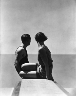 Black and white image of two bathers, male and female, on a diving board.