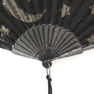 Pleated fan. Silk leaf completely embroidered with black and silver spangles showing a moon and stars. Ebony sticks inlaid with steel piqués. Metal bail, black silk tassel and mother-of-pearl washer at rivet.