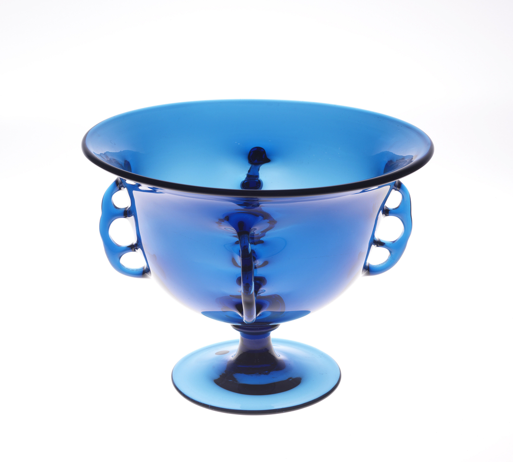 Thin, cobalt blue, blown glass fruit bowl with knob on stem and four tooled handles each with three finger holes.