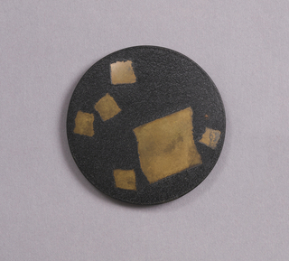 Circular form, black ground decorated with six irregular gold squares of different sizes.