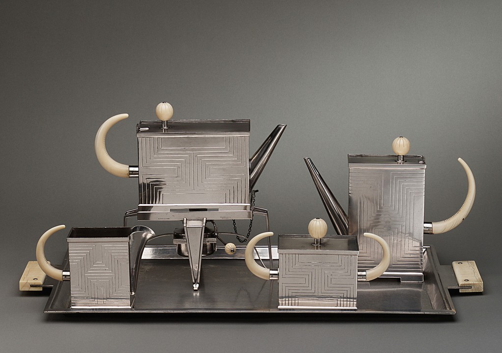 Rectilinear tea set consisting of two pitchers, creamer, sugar bowl and tray; pieces are incised with symmetrical geometric pattern while their finials and handles are articulated in ivory.