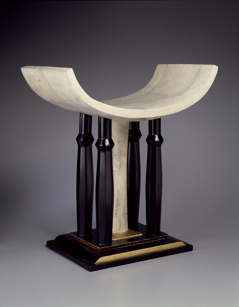 Stool with rectangular base and curved seat.