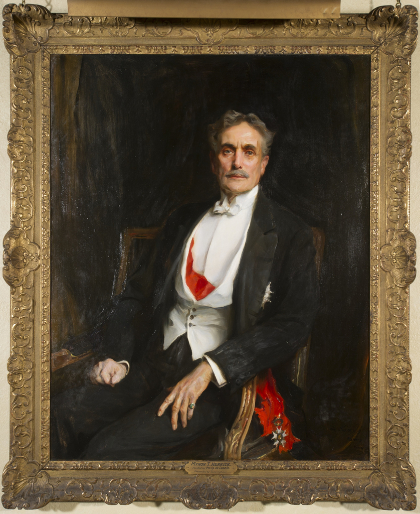 Seated portrait of Myron Herrick rendered in oil on canvas; the sitter is positioned at an angle but looks straight out at the viewer, wearing formal attire with medals and seated in a gilt wood armchair. Incased by giltwood frame with egg-and-dart, vegetal, and rocaille decoration.