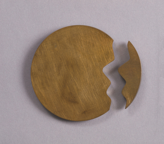 Gold-toned, slightly domed brooch of two parts, one large, one small, that fit together along a jagged  edge to form a circle.