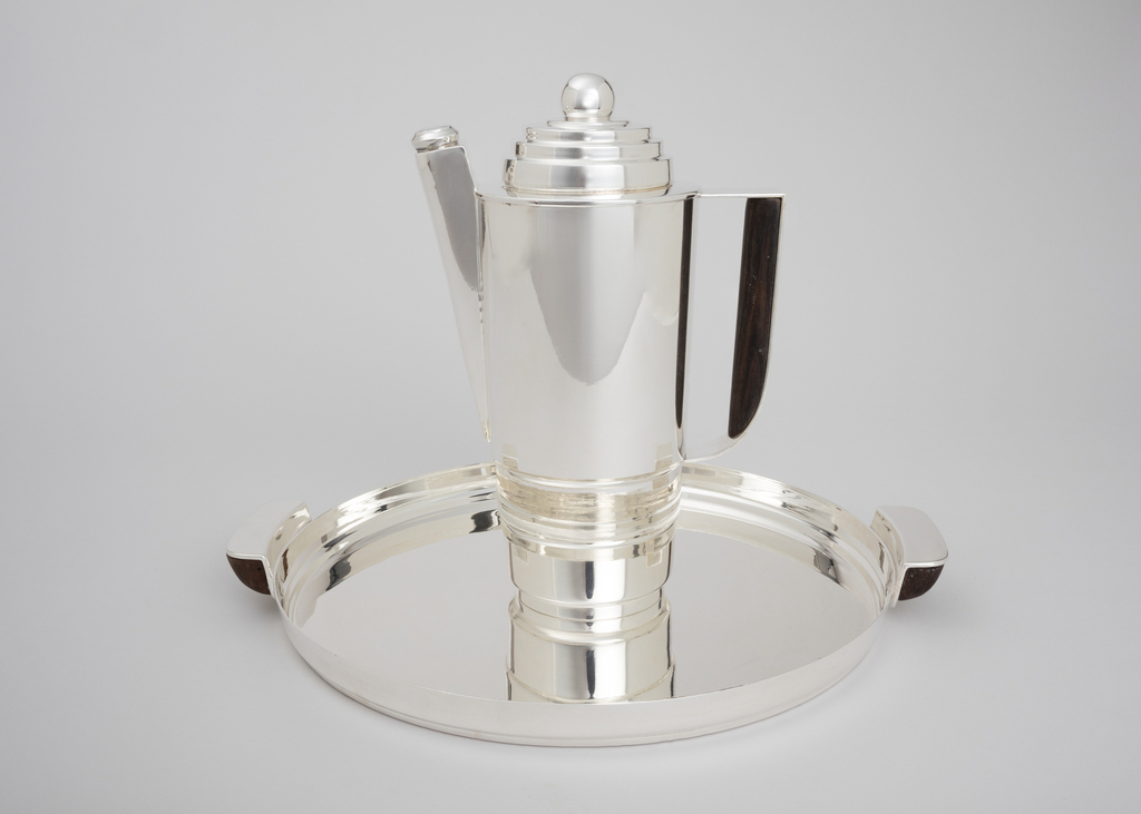 Circular tray with raised lip. Rectangular handles with rounded edges.