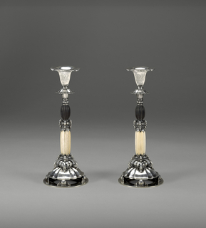 Pair of candlesticks featuring monogrammed sterling silver holders upon cast sterling silver elements stacked with fluted ebony and ivory lozenges terminating in cast silver volutes atop inverted scalloped semi-spheres supported by gourd-like volumes around the rim of a disc-shaped base.