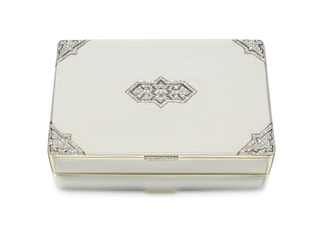 Cigar or cigarette box decorated on the front with white enamel stripes, the four corners and  center accented by openwork diamond geometric plaques of Oriental influence, the sides applied with rectangular sections of white enamel stripes, with diamnd-set thumbpiece; mounted in gold and platinum