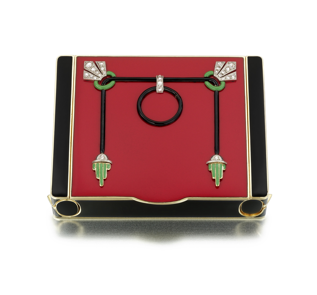 Vanity case of black and red lacquer, front decorated with a stylized gong motif; interior fitted with large compartment with sliding lipstick holder and perfume baton on either side