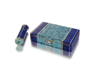 Rectangular case featuring a central motif composed of square turquoise segments set diagonally, flanked by bands of lapis lazuli, the front and back sides also with bands, the ends set with lapis lazuli, with diamond and sapphire thumbpiece; with matching lipstick baton with detachable fluted lipstick holder