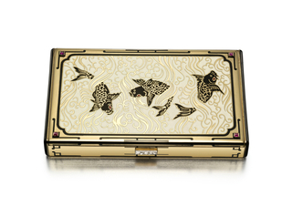 Vanity case featuring black enamel koi with red enamel eyes in cream and gold enamel water, outlined in black enamel with rubies at corners, underside of the case featuring a gold placque of Persian design engraved with lines on a white enamel ground outlined in black enamel; push button clasp set with rose-cut diamonds; interior with two compartments for powder, detachable lipstick holder, fitted mirror