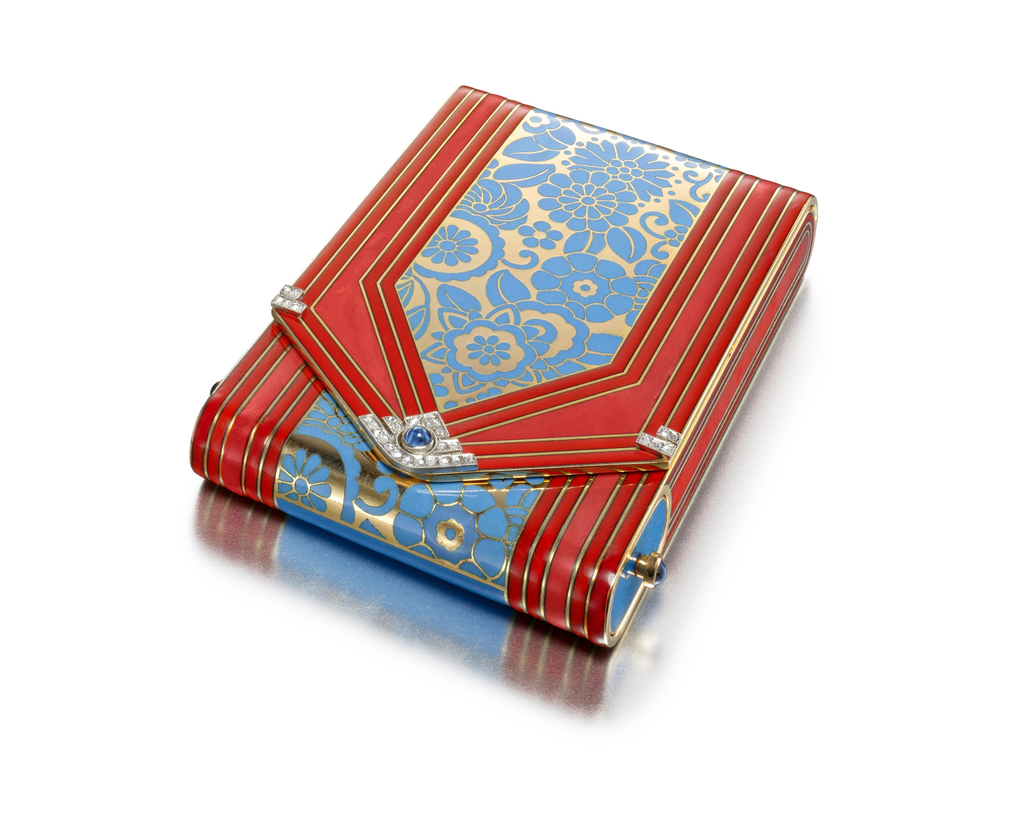 Vanity case of envelope design accented in the center by a blue enamel floral motif sided by bands of red enamel, accented with three cabochon sapphires at the front and sides, the reverse with a blue enamel center