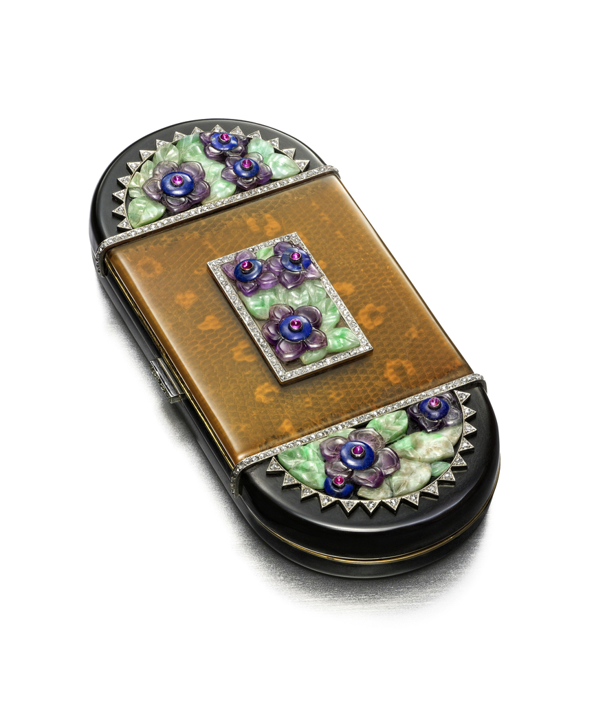 Vanity case with an amber-covered snakeskin panel centering a rectangle of anemone flowers, the rectangle outlined with diamnds, with rounded black enamel terminals decorated with hardstone flowers, with a diamond-set button clasp; interior with a powder compartment and a fitted mirror