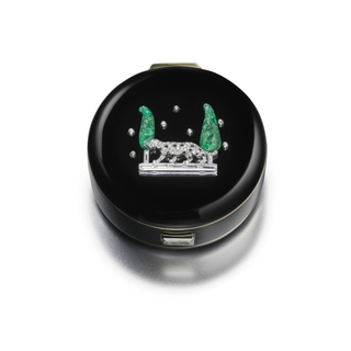 circular cylindrical formwith cushion top set with a figure of a panther in diamonds and onyx between two carved emerald cypress trees