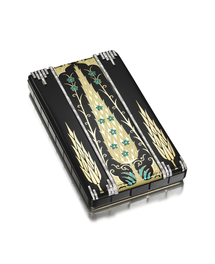 Vanity case decorated with three stylized gold cypress trees, the center tree applied with cream-colored enamel accented by turquiose enamel flowers and grass, partially framed by ornate foliate sections, all within a black enamel ground with bands of diamonds, the reverse applied with a modified black enamel lozenge motif accented by small flowers, the sides set with onyx panels; the interior with a fitted mirror, two powder compartments and a lipstick tube; mounted in gold and platinum