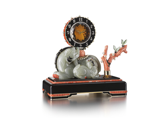 A clock designed as a carved nephrite Chinese Imperial guardian lion and a young lion, the carved lion embellished with black enamel and gold mane and red enamel toenails, with eyes of cabochon emeralds for the large lion and cabochon rubies for the young lion, supporting a circular clock with carved citrine face, rose-cut diamond-set hands in the shape of a dragon and black enameled chapter ring with rose-cut diamond Arabic numerals stylized as Chinese calligraphy, the red enamel border studded with pearls, all atop a carved coral ball resting on a pearl-fringed saddle blanket atop the guardian lion, beside a carved coral branch with carved stone leaves and pearls, supported by a base of black-enameled gold accented with calibre-cut corals; mounted in platinum and gold; with original green leather Cartier case.