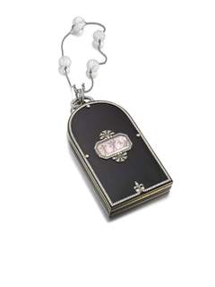 Vanity case rounded at one end, with hexagonal mother-of-pearl panel depicting putti surrounded by round diamonds, loops set with round diamonds connect to a chain with four fluted rock crystal beads, interior with two compartments, central detachable lip-stick holder, and a fitted mirror
