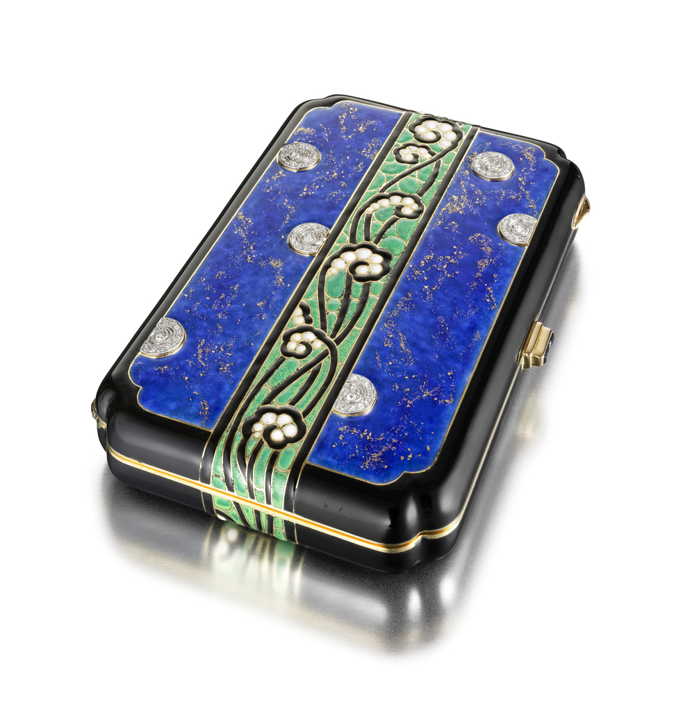 Compact applied with blue and gold enamel replicated lapis lazuli, centering upon a continuous band depicting a meandering motif of stylized fern fronds applied with black, green, and white enamel, the front accented by circular placques set with rose-cut diamonds, edged with black enamel; interior fitted with a mirror and compartment