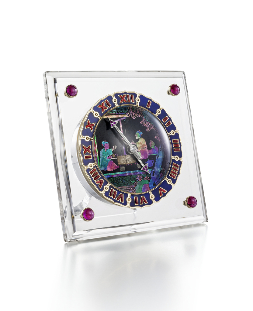 A square panel of rock crystal with molded edges framing a circular dial of Chinese lacquer inlaid with tinted mother-of-pearl antique Chinese panel depicting figures at a loom, within a shaped bezel of deep blue enamel with orange translucent enamel Roman numerals, rose-cut diamond and ruby arrow hands, each corner inset with a cabochon ruby in a gold bezel, completed by a folding strut